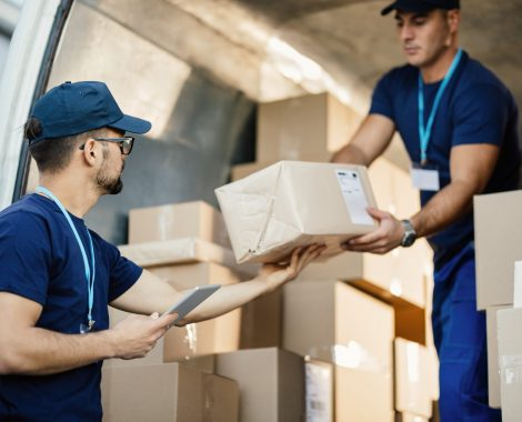Young,Courier,Using,Touchpad,While,Loading,Packages,With,His,Coworker
